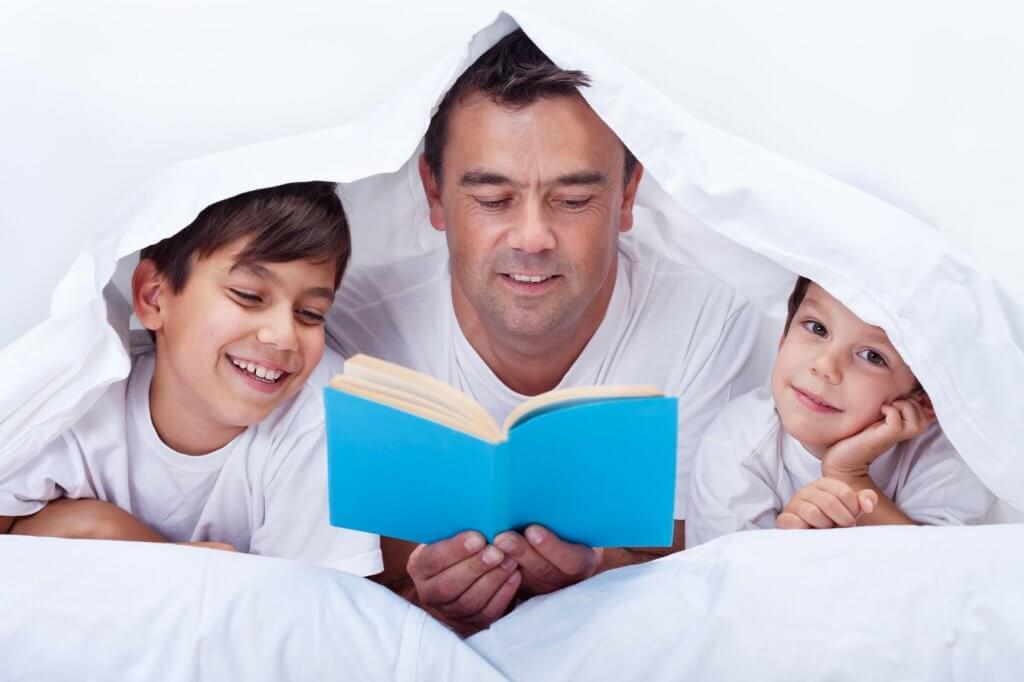 Père qui lit une histoire avec ses garçons.